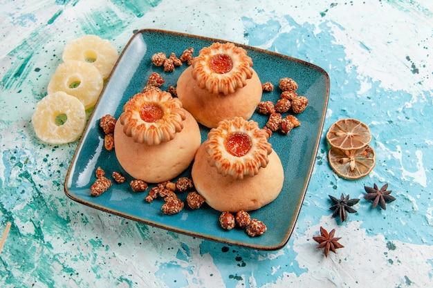 水色の表面に乾燥パイナップルリングが付いたハーフトップビューのおいしいクッキークッキービスケットスイートシュガーカラー