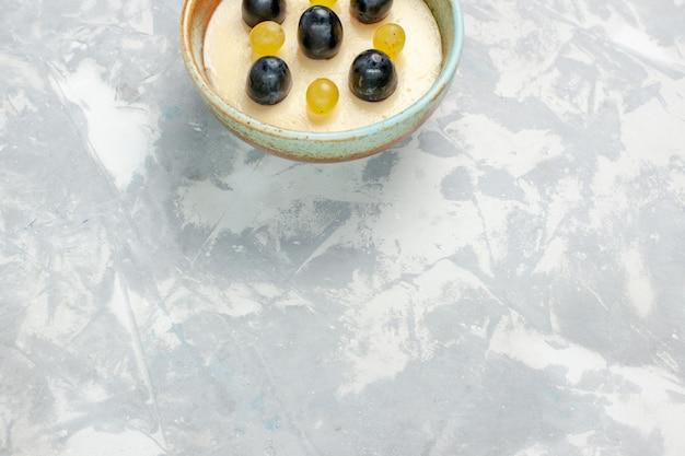 Vista dall'alto delizioso dessert cremoso con frutta in cima all'interno di una piccola pentola sulla superficie bianca