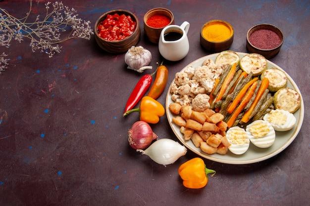 Delizioso pasto a base di uova con verdure cotte e condimenti sullo spazio buio