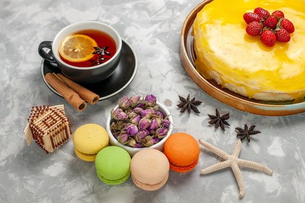 Vista dall'alto una deliziosa torta fruttata con macarons francesi di sciroppo giallo e tazza di tè sulla scrivania bianca