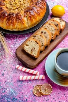 ライトピンクの表面にコーヒーカップでスライスしたハーフトップビューのおいしいレーズンケーキパイシュガースイートビスケットクッキーの色を焼く