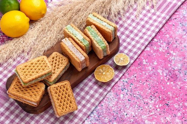 ピンクの机の上にレモンとシナモンが入ったハーフトップビューのおいしいサンドイッチクッキー。