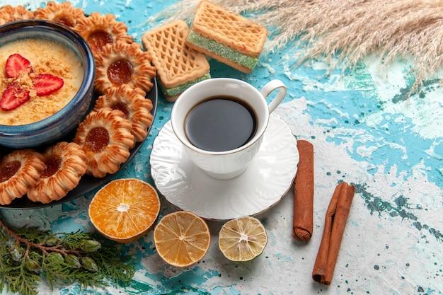 Вид сверху на вкусное сахарное печенье с вафлями чашка кофе и клубничный десерт на синей поверхности печенье бисквит сладкий торт десертный цвет