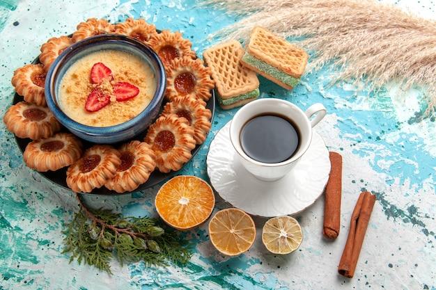 青い表面にワッフルカップのコーヒーとストロベリーデザートが付いたハーフトップビューのおいしいシュガークッキークッキービスケットスイートケーキデザートカラー