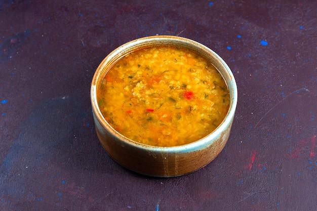 暗い机の上の丸いプレートの中のハーフトップビューのおいしい野菜スープ。