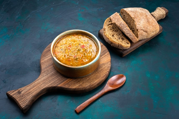 Вкусный овощной суп в круглой тарелке с хлебом на темно-синем столе, вид сверху наполовину.