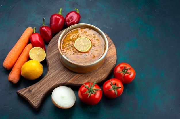Vista dall'alto una deliziosa zuppa di verdure all'interno del piatto rotondo con limone e verdure fresche sulla scrivania blu scuro.