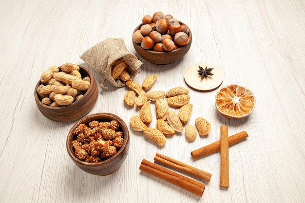 Half-top view different nuts with cinnamon on the white desk nut snack walnut hazelnut