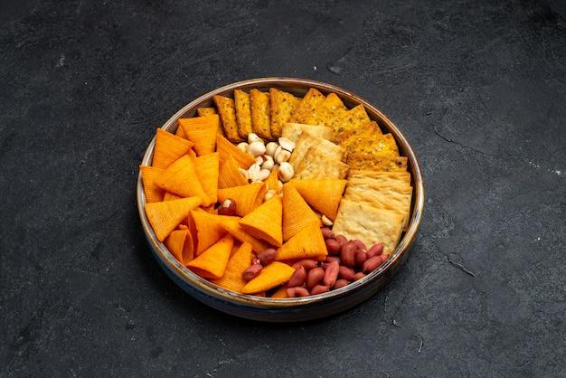 Вид сверху на разные закуски, крекеры, орехи и чипсы на темно-серой поверхности, закуска, хрустящие крекеры, соль