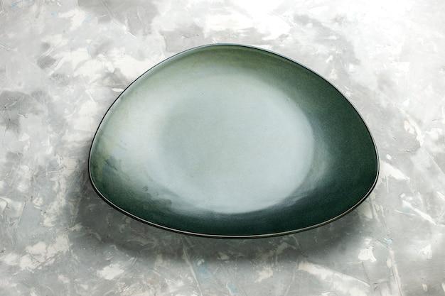 밝은 회색 책상에 고립 된 절반 가기보기 빈 녹색 접시.