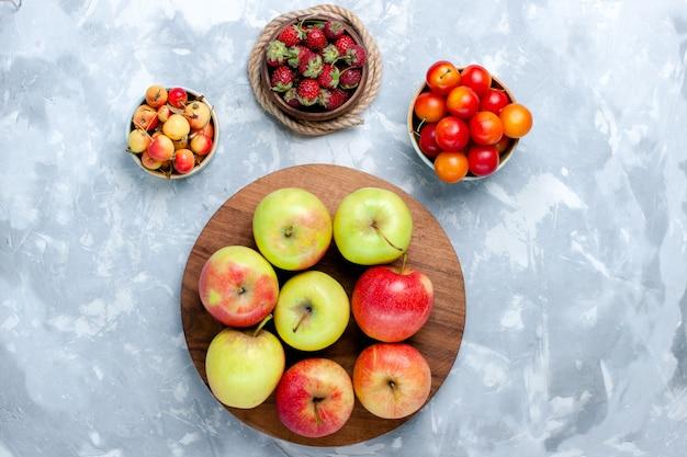 Половина сверху свежие яблоки спелые спелые фрукты на светлом белом столе фрукты еда витаминный цвет свежее дерево