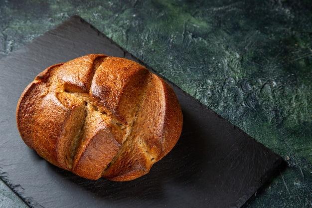 暗い机の上にハーフトップビューの焼きたてのおいしいパン