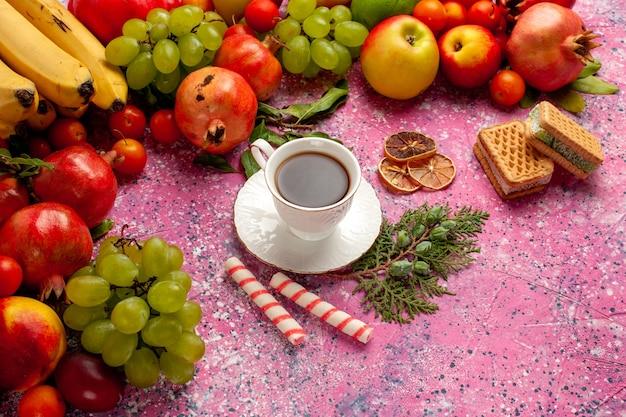 Frutta variopinta della composizione nella frutta fresca di vista mezza superiore con la tazza di tè e le cialde sulla parete rosa frutta fresca dell'albero di colore dolce maturo