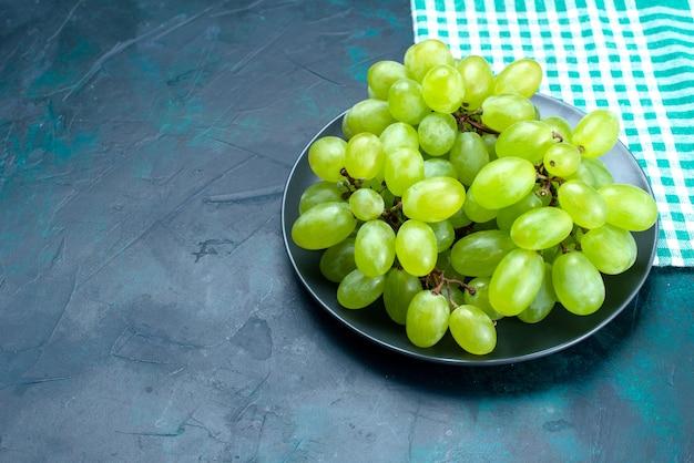 Frutti succosi pastosi dell'uva verde fresca di mezza vista superiore all'interno del piatto sullo scrittorio blu scuro.