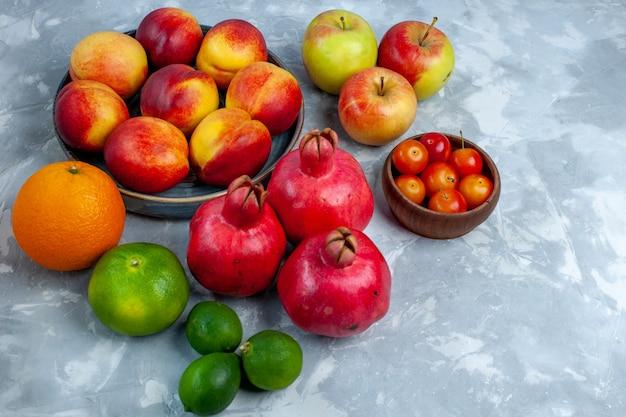 Vista dall'alto di pesche fresche deliziosi frutti estivi con mandarini e mela sulla scrivania bianco-chiaro frutta fresca vitamina mellow albero maturo
