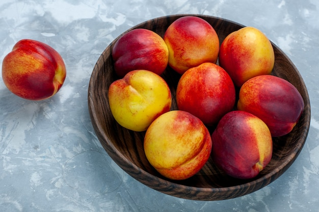 Pesche fresche di mezza vista con frutti morbidi e gustosi all'interno del piatto marrone sulla scrivania bianco-chiaro, frutta fresca, foto, vitamina