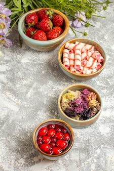 Fragole rosse fresche di vista mezza superiore con i fiori sulla caramella rossa della frutta di bacca di superficie bianca