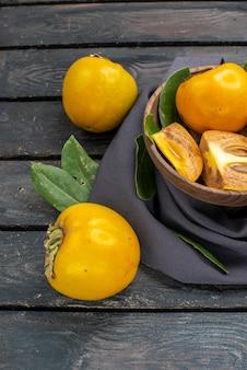木製のテーブルの上に新鮮な甘い柿のハーフトップビュー、熟したフルーツのまろやか