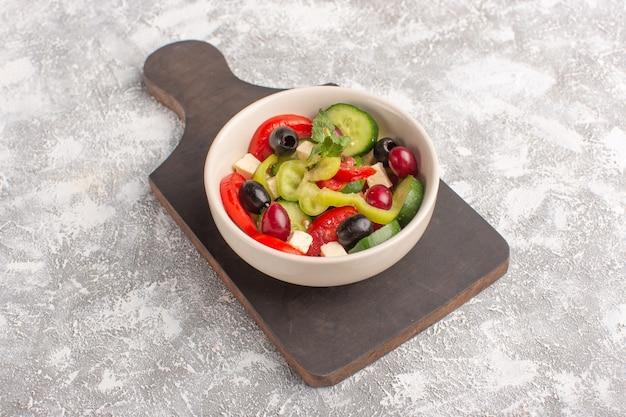 Салат из свежих овощей с нарезанными огурцами, помидорами, оливками и белым сыром, вид сверху на тарелке на сером столе, салат из овощей, еда, цвет еды