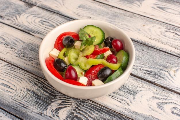Салат из свежих овощей с нарезанными огурцами, помидоры, оливковое внутри тарелки на серой поверхности, вид сверху, салат из овощей, цвет еды