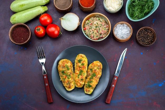 濃い紫色の机の上に、グリーンミンチ肉で調理したカボチャと調味料を添えたハーフトップビューの新鮮な野菜。