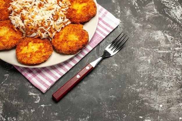 暗い表面の肉のリッソール皿にご飯とカツレツのハーフトップビュー
