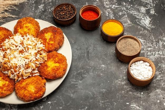 Cotolette fritte con vista dall'alto a metà con riso cotto e condimenti su un piatto di carne di cibo di superficie scura