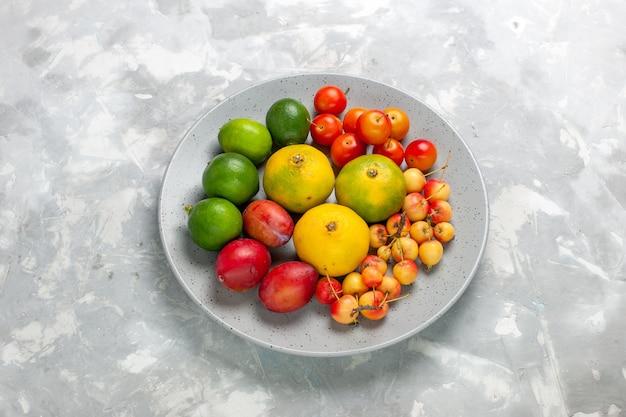 밝은 회색 책상에 접시 안에 절반 상위 뷰 과일 구성 감귤 레몬 자두.