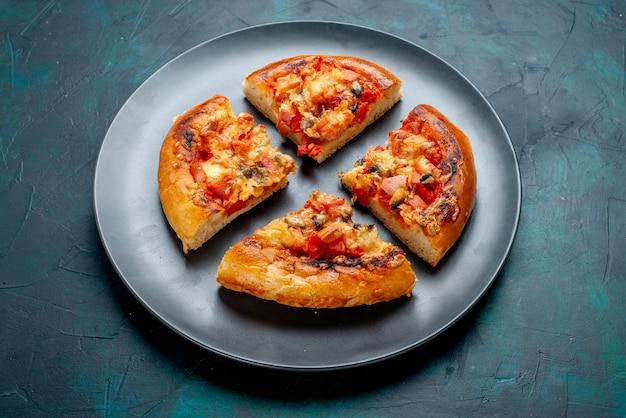 Pizza al formaggio a metà vista dall'alto quattro fette di piatto interno sulla scrivania blu scuro.