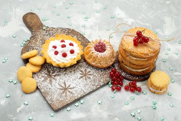 Vista a metà superiore torte piccole con crema e biscotti sandwich sulla superficie leggera dolce