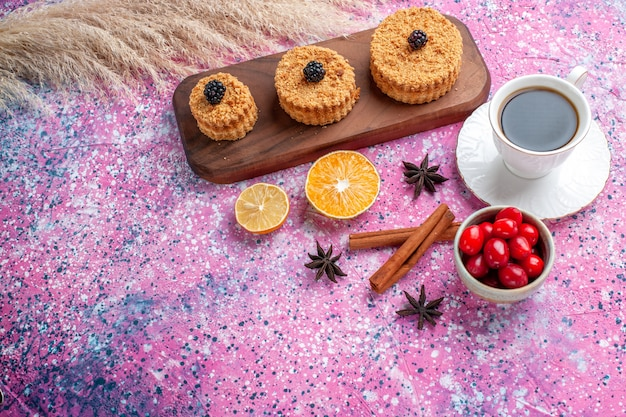 Half-top view of little delicious cakes with cinnamon and cup of tea on light pink surface