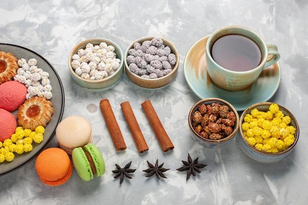 Vista dall'alto piccole torte deliziose con biscotti, tè e caramelle sulla scrivania bianca