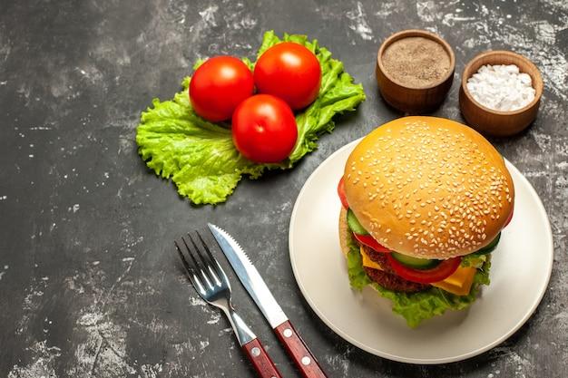 ダークサーフェスのバンズサンドイッチファーストフードに野菜とサラダを添えたハーフトップビューのミートバーガー