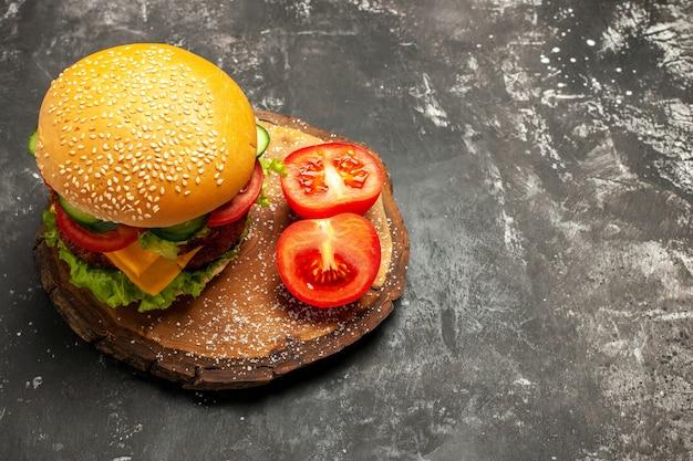 Мясной бургер с овощами на темной поверхности, вид сверху, булочка, фаст-фуд