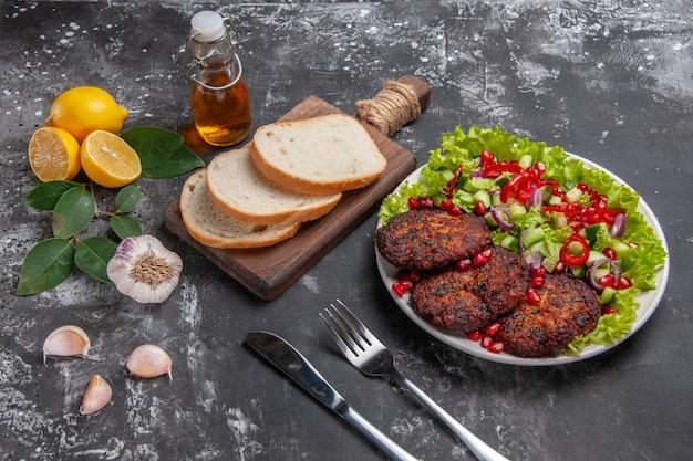 Мясные котлеты с салатом и хлебом, вид сверху до половины