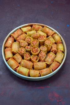暗い机の上の鍋の中で野菜と一緒に巻かれたハーフトップビューの肉ロール肉夕食食品食事野菜