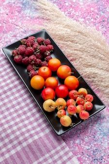 핑크색 표면에 검은 색 형태로 신선한 과일 나무 딸기와 자두의 절반 평면도