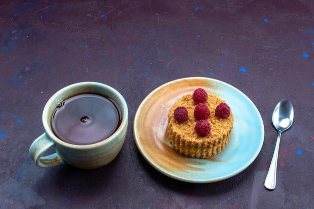 紺色の表面にお茶を入れたプレートの中に新鮮なラズベリーが入った小さな丸いケーキのハーフトップビュー