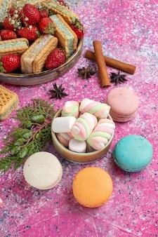 Вид сверху на вкусное вафельное печенье с макаронами и свежей красной клубникой на розовой поверхности