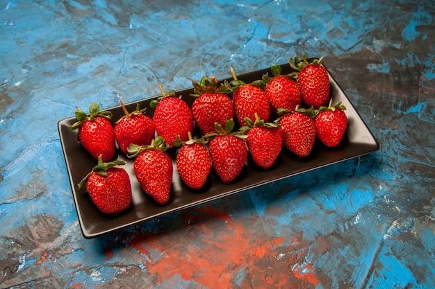 Красная клубника внутри черной сковороды на синем фоне, вид сверху на красный цвет дикого дерева, летние ягоды, фото