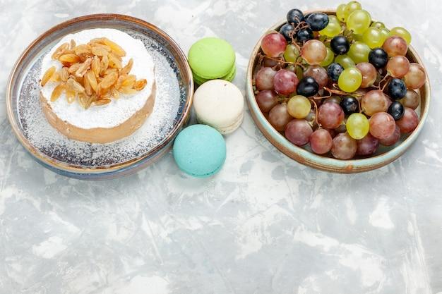 ハーフトップビュー丸い小さなケーキシュガーレーズンフレンチマカロンと白い机の上のブドウ粉砂糖甘いビスケットケーキクリームパイ