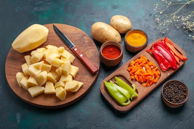 Вид сверху нарезанный свежий картофель с приправами и нарезанный перец на темно-синей поверхности