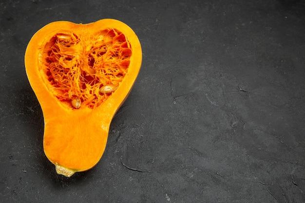 ハーフトップビュースライスした新鮮なカボチャの暗いテーブルの写真フルーツオレンジ