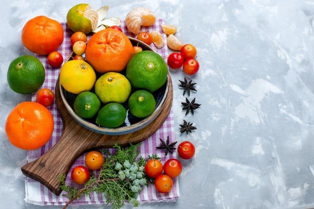 Кислые свежие мандарины с лимонами и сливами на белом столе, вид сверху, цитрусовые, экзотические, тропические фрукты, витамин кислый