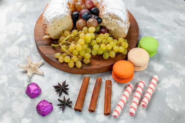 Torta in polvere di zucchero a metà vista superiore con uva cannella e macarons sulla superficie bianca torta di zucchero dolce cuocere il biscotto