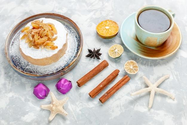 Vista mezza dall'alto zucchero uvetta in polvere uva secca sulla parte superiore della piccola torta con tè e cannella sulla scrivania bianca zucchero uvetta torta dolce torta biscotto