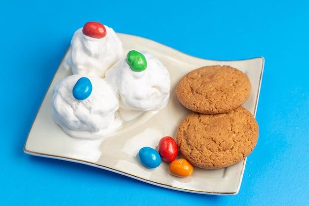 青い机の上のプレートの中においしいアイスクリームが付いたハーフトップビューの甘いクッキー