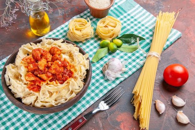 ダークフロアのパスタ料理にチキンとソースを添えたハーフトップビューのおいしい調理済み生地