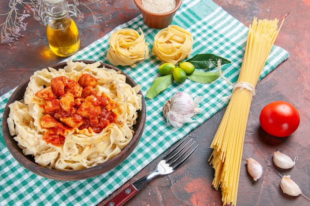 Impasto cucinato gustoso con vista dall'alto a metà con pollo e salsa sul piatto di pasta piano scuro