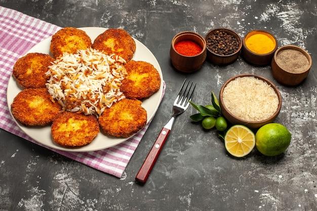 Vista dall'alto gustose cotolette fritte con riso e condimenti su polpette di carne con superficie scura